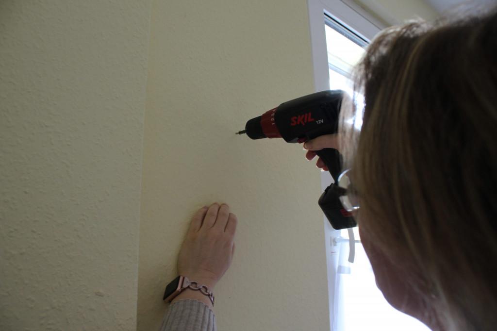 Frau mit Akkuschrauber im Einsatz an der Wand