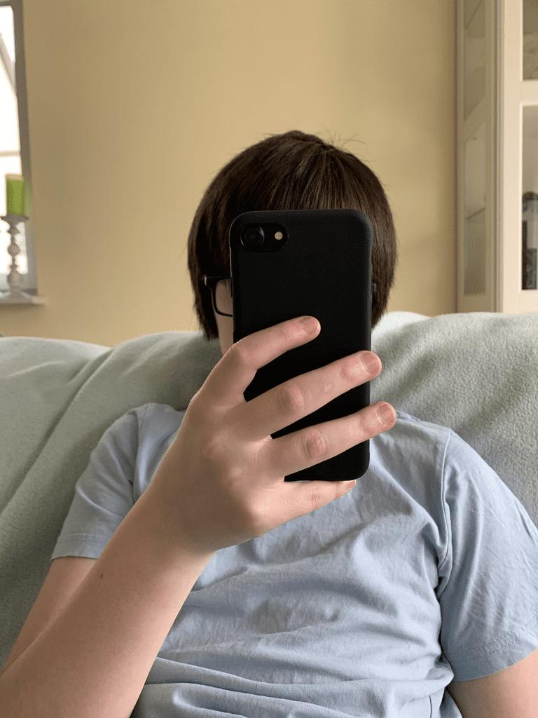Kind mit Handy im Gesicht